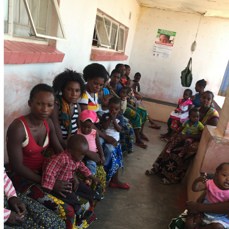 simonga_clinic_waiting_room_outdoors_concrete_area_moms_and_babies