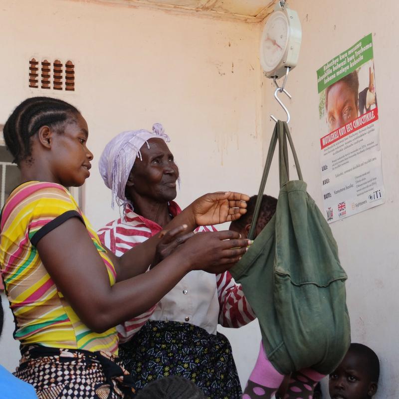 simonga_clinic_zambia_mom_and_volunteer_weighing_baby