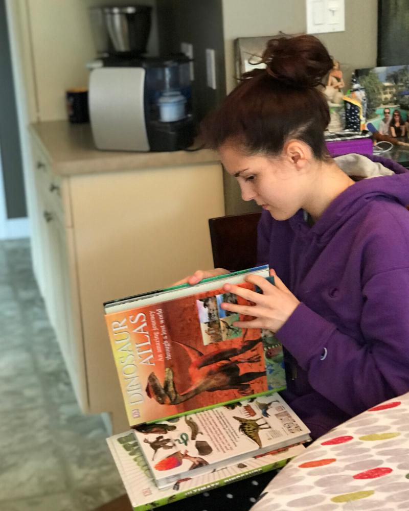 teen_reading_dinosaur_books
