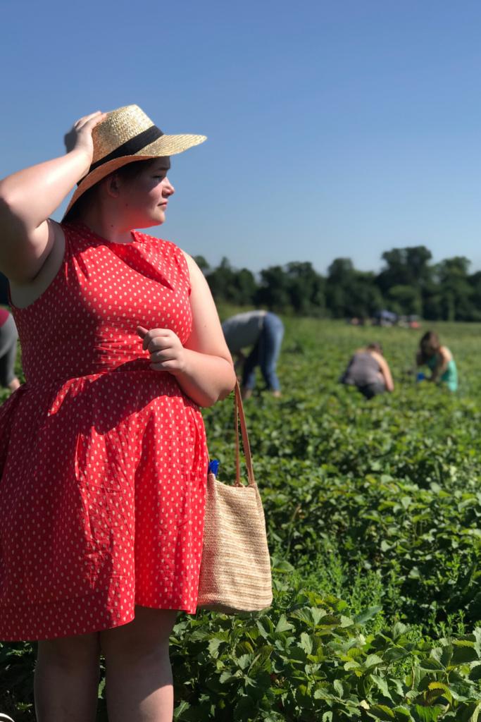 girl_wearing_red_dress_standing_in_strawberry_field