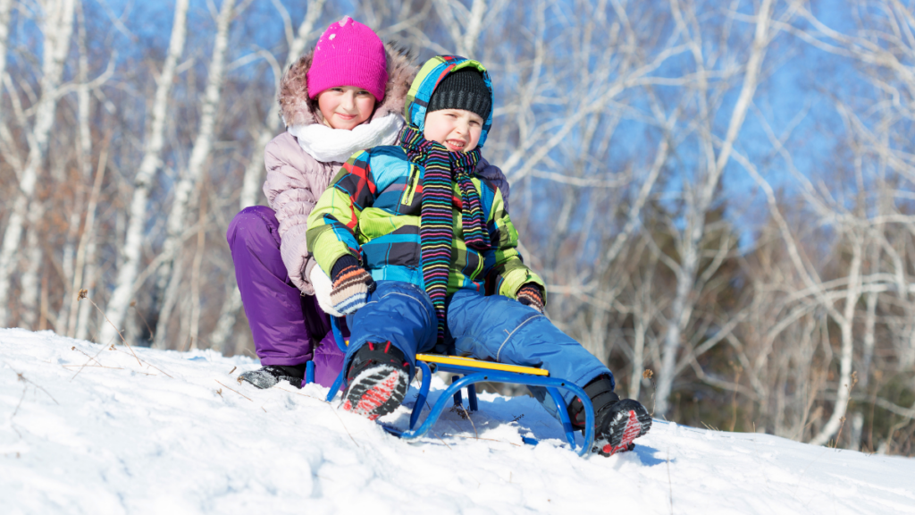 two_young_kids_on_sled_in_winter