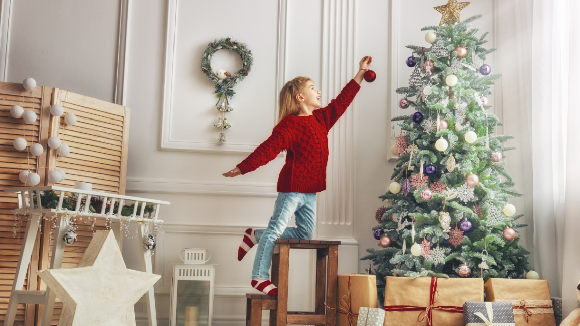 christmas_tree_girl_standing_on_chair_to_reach_tree