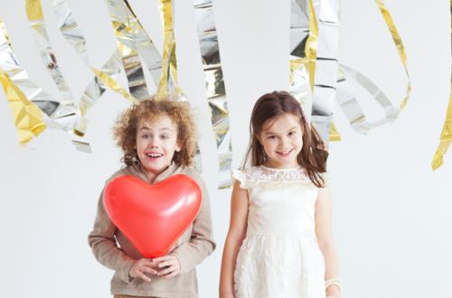 valentine_boy_holding_red_heart_girl_under_streamers