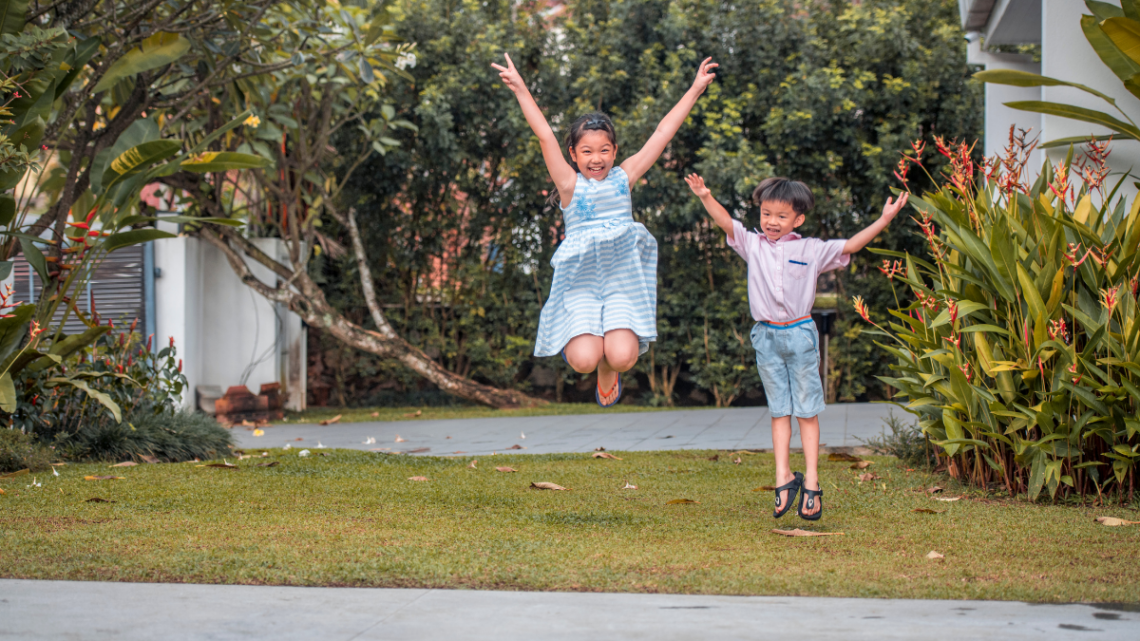 kids_jumping_in_summer_on_front_lawn