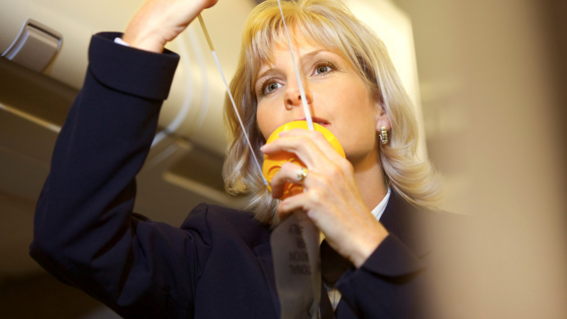 airline_attendant_demonstrating_oxygen_mask